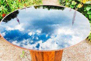 The beautiful reflection of the sky can be seen on this reflecting pool bird bath